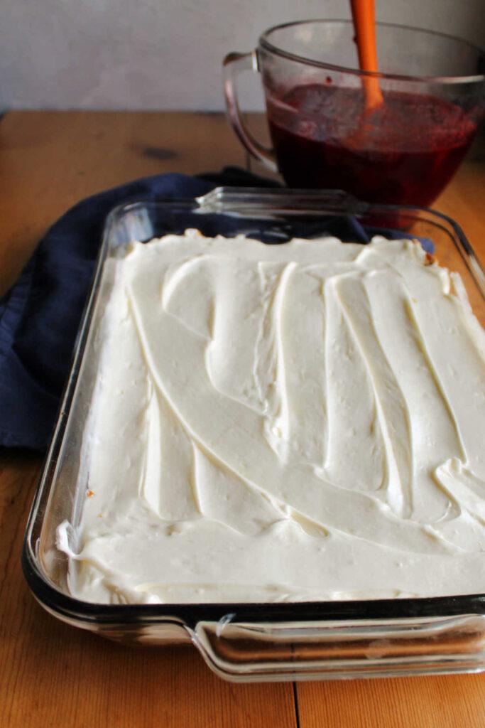 Cream cheese filling spread over pretzel crust with bowl of strawberry jello in background.