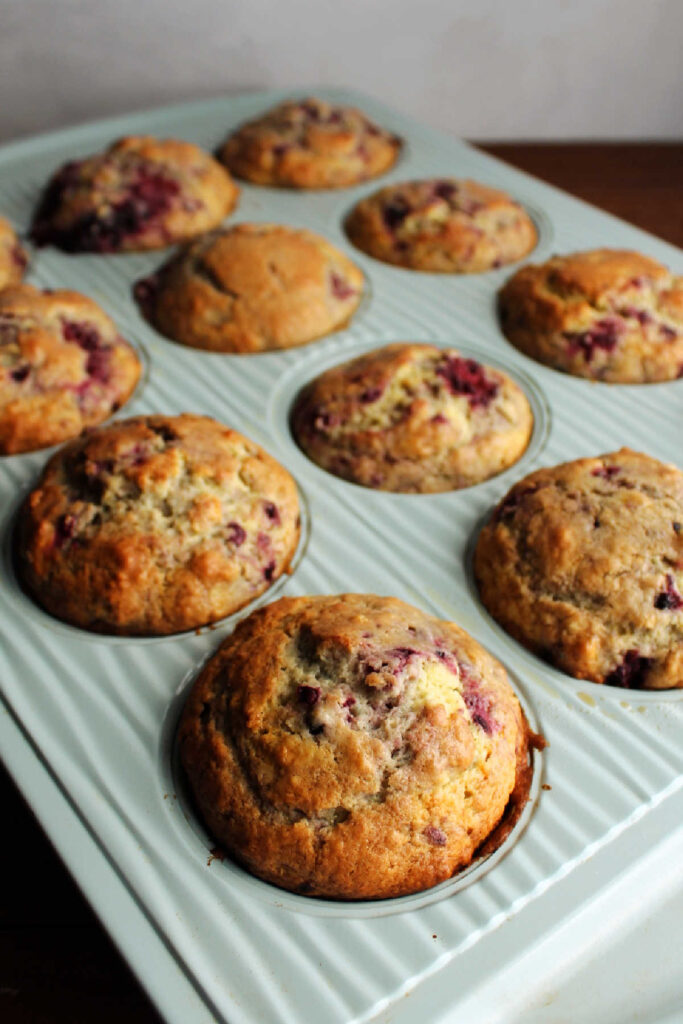 Muffin pan filled with freshly baked blackberry sour cream muffins.
