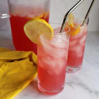 Glasses of pink lemonade on ice.