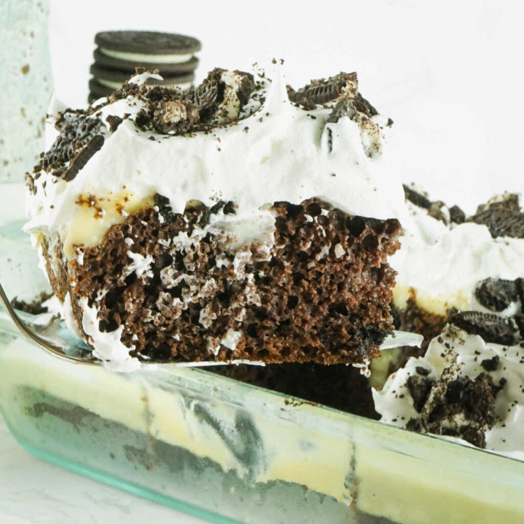 Lifting piece of Oreo cheesecake poke cake out of pan.