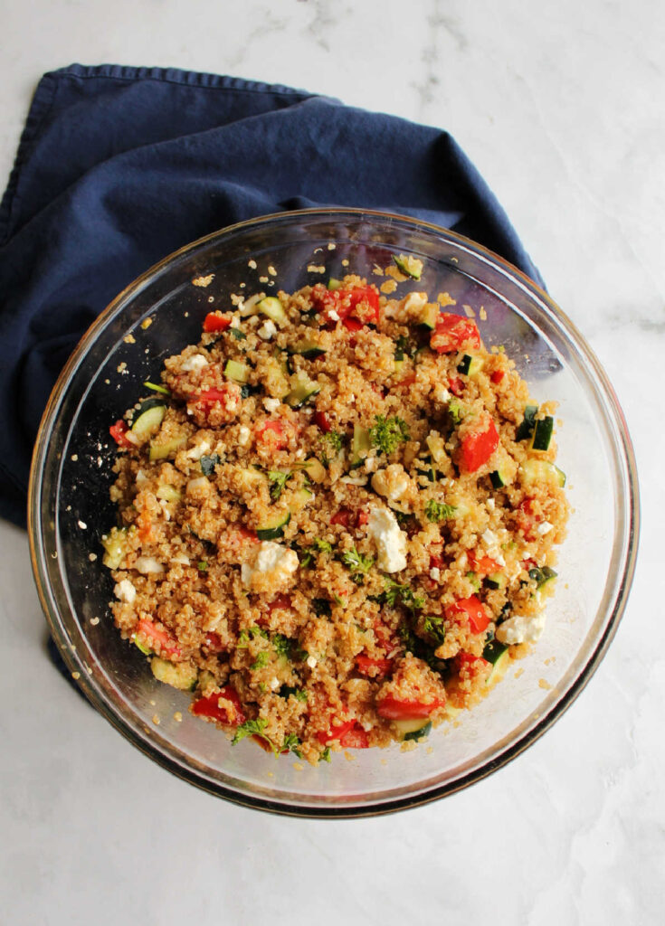 Big mixing bowl filled with tomatoes, cucumbers, quinoa, dressing, cheese, herbs and more.