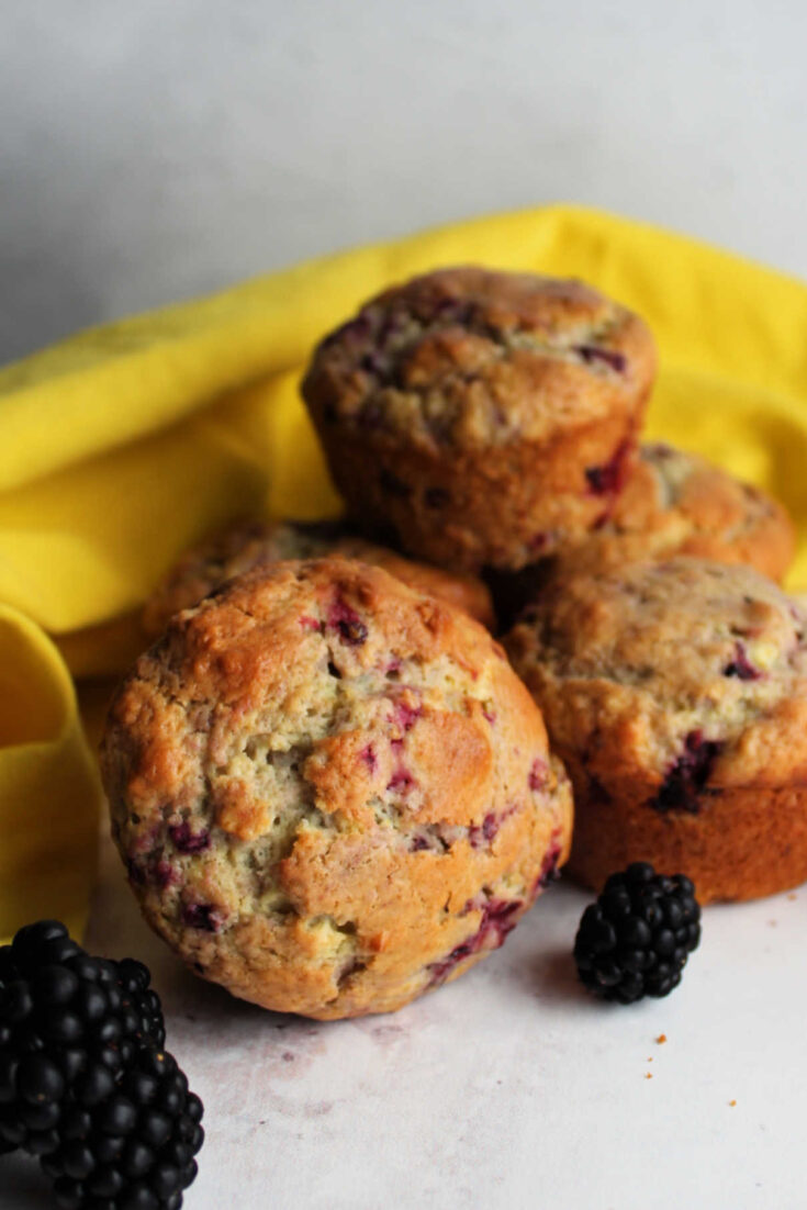 Stack of tender blackberry muffins ready to eat.