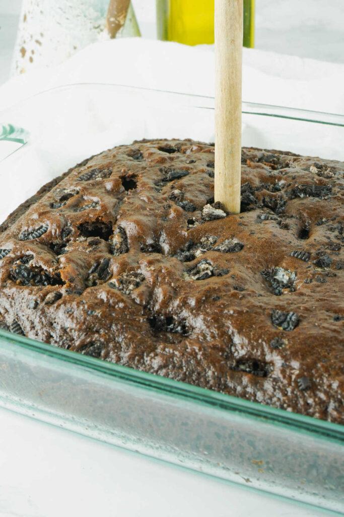 Poking holes in freshly baked chocolate cake.