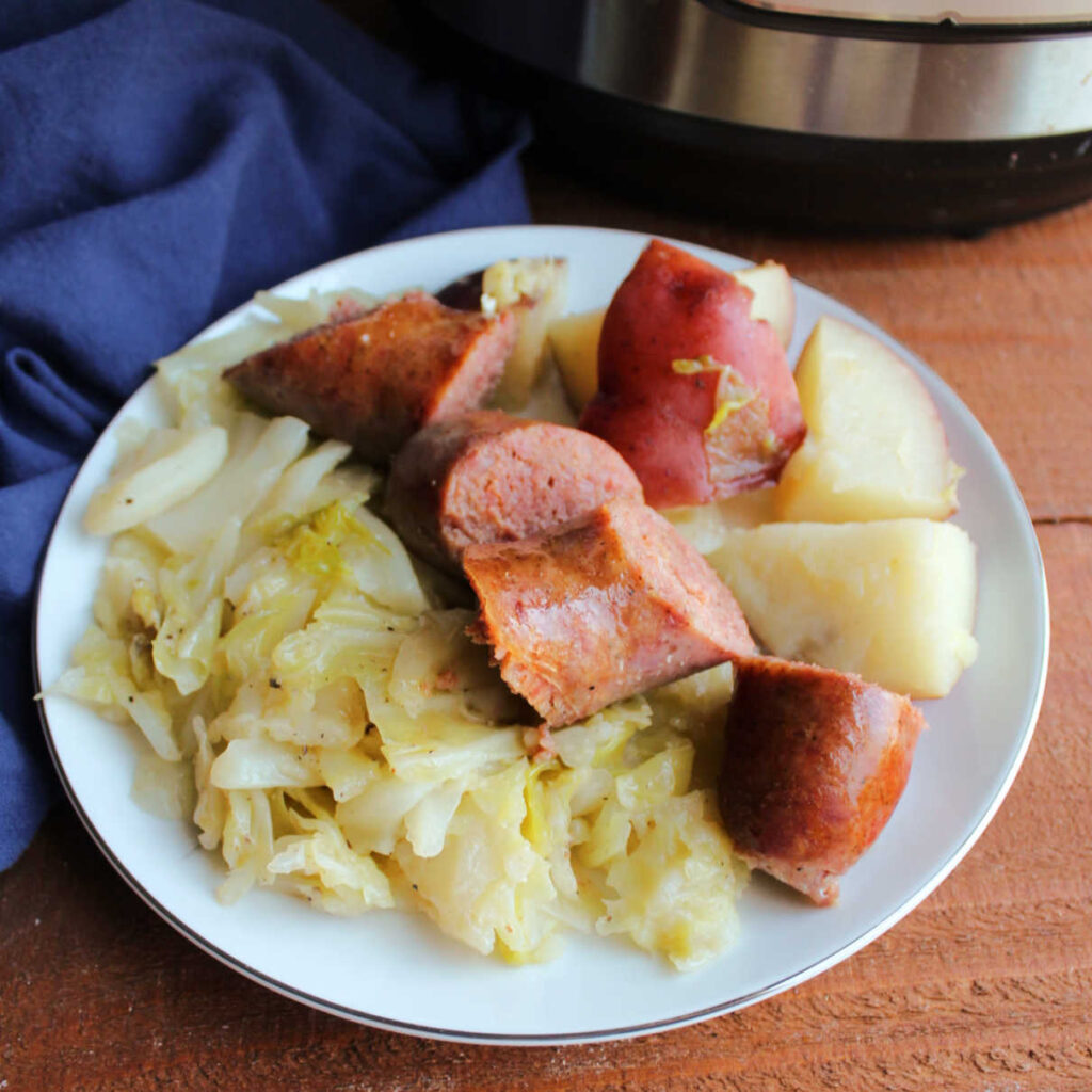 Plate filled with cooked sausage, potatoes and cabbage.