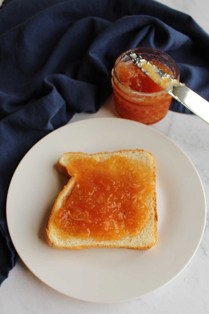 strawberry zucchini jam spread over slice of toast.
