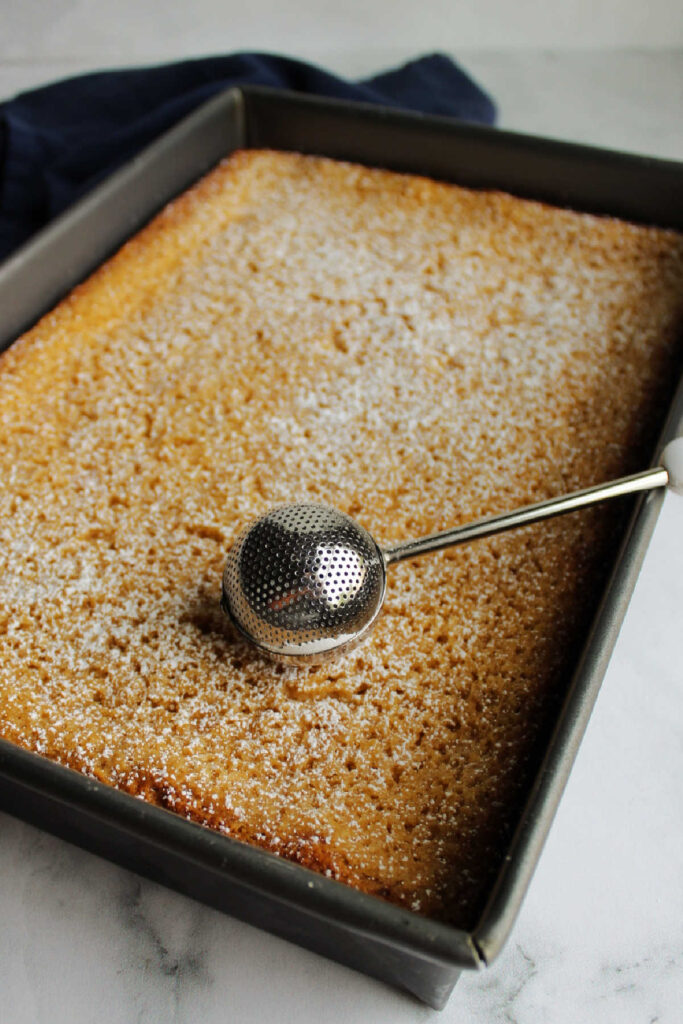 Dusting powdered sugar over cooled apple gooey butter cake.