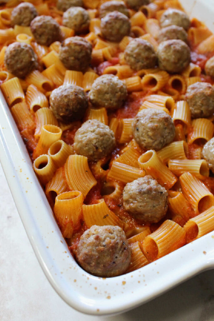 Cooked pasta and meatball casserole ready for cheese topping.