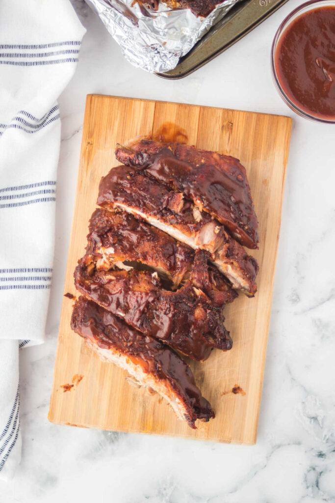 BBQ sauce coated ribs on wood cutting board.