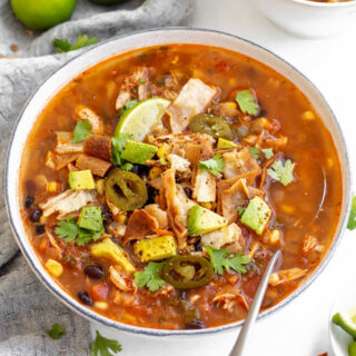 Bowl of chunky chicken tortilla soup topped with tortilla strips, jalapenos, avocado, a lime wedge and cilantro.