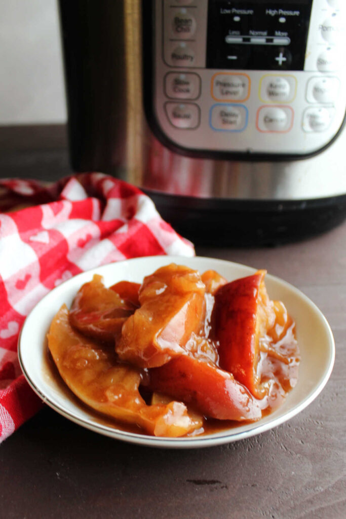 Bowl of cooked apples in thick cinnamon brown sugar sauce in bowl in front of instant pot.