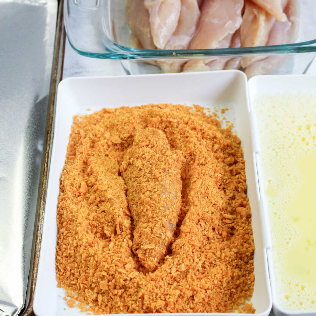 Chicken finger dipped in egg wash and rolled in cheese cracker crumbs.
