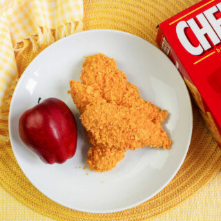 plate of cheez-it coated chicken fingers and apple ready to eat.