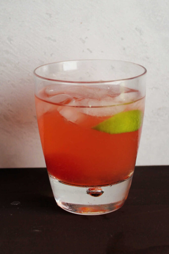Glass of pink cherry limeade with cherry and slice of lime inside.