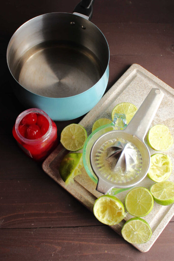 Limes, maraschino cherries and sugar water ready to be made into limeade.