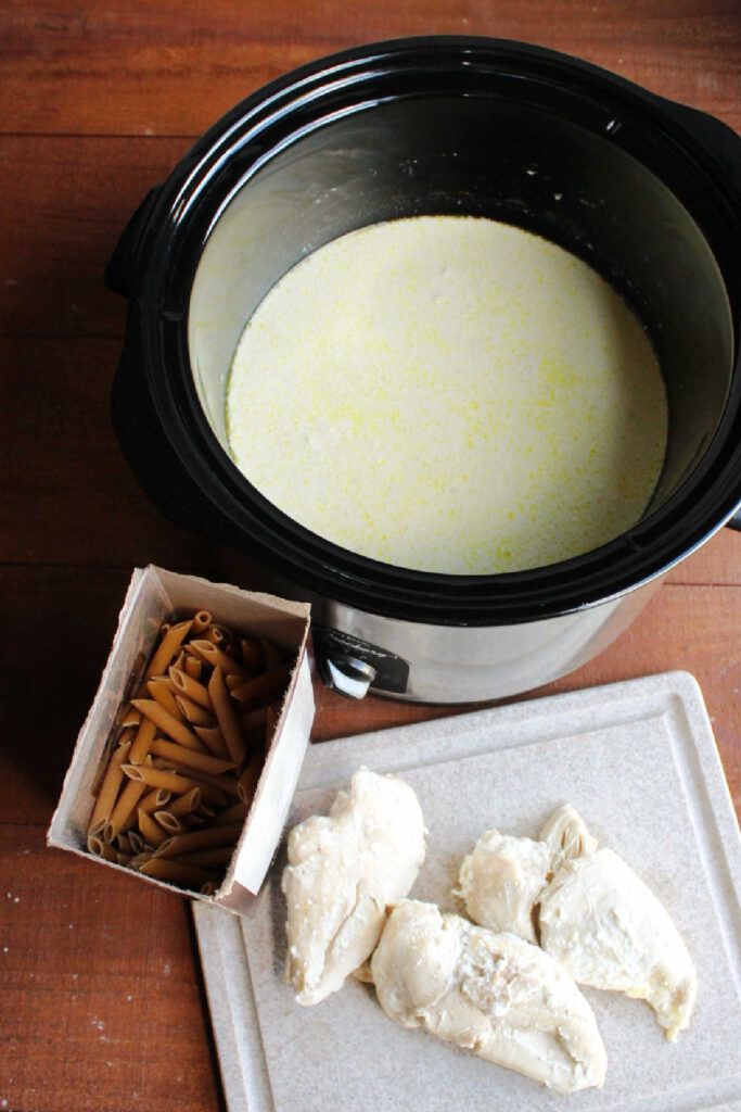 Cooked chicken on cutting board next to crock pot full of creamy mixture and box of pasta.