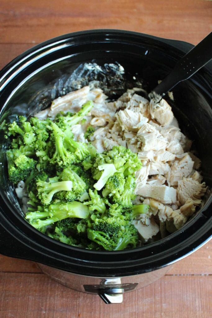 Chicken and broccoli added to crock pot of cooked creamy pasta.