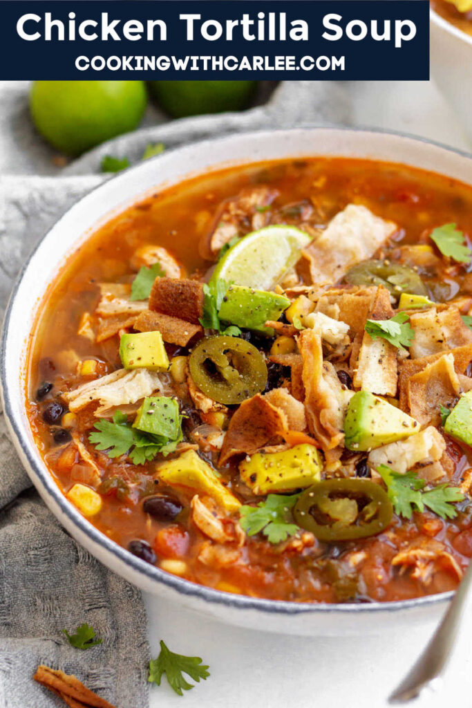 Chicken Tortilla Soup is a cozy & filling soup recipe full of shredded chicken, corn, beans and other delicious ingredients that are simmered in a tomato base. Top the soup generously with homemade tortilla chips, cilantro, avocado, lime and a dollop of sour cream and you got yourself a perfect Mexican-inspired soup which is the perfect easy weeknight dinner.