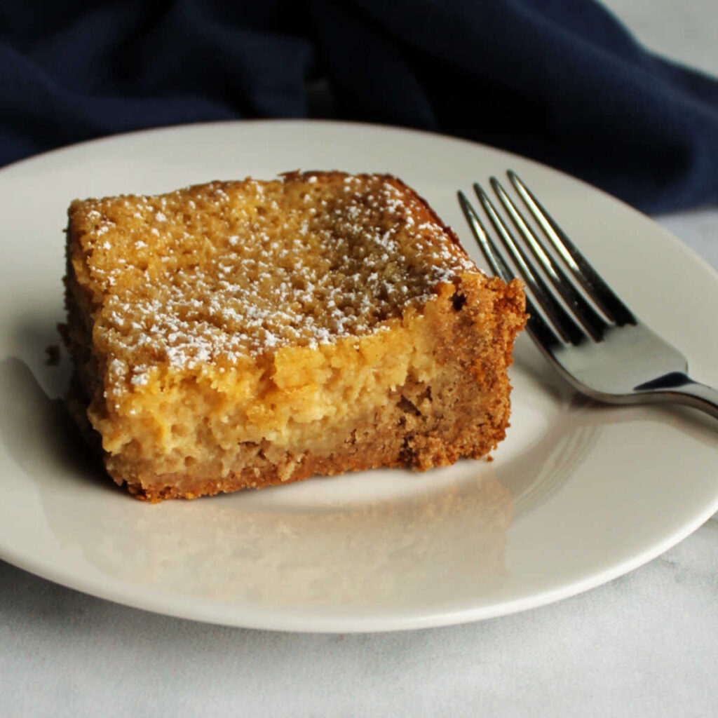 Piece of apple spice gooey butter cake with cakey crust and creamy filling.