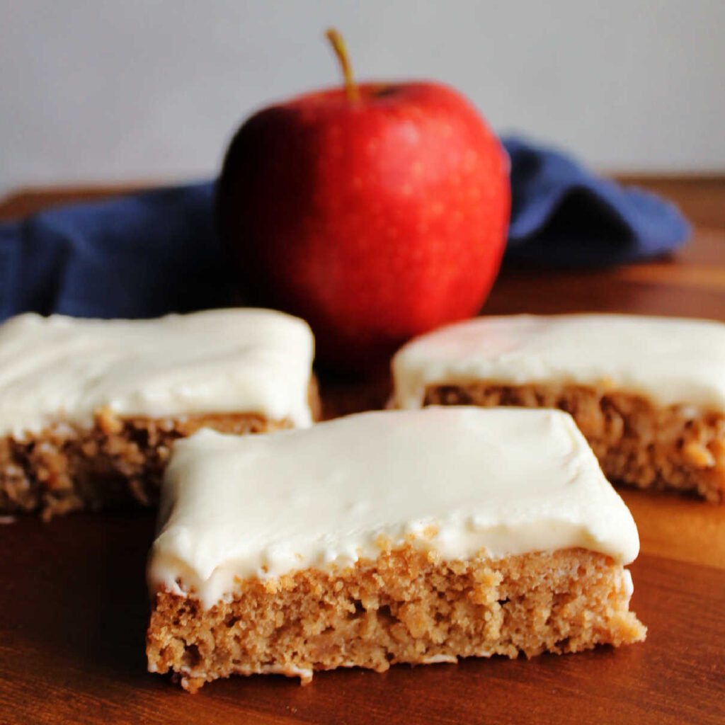 Pieces of applesauce cake topped with soft white sour cream frosting with an apple in the background.