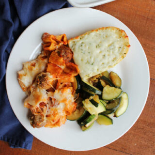 Dinner plate with no boil rigatoni and meatballs, sauteed zucchini and a hunk of cheesy garlic bread.