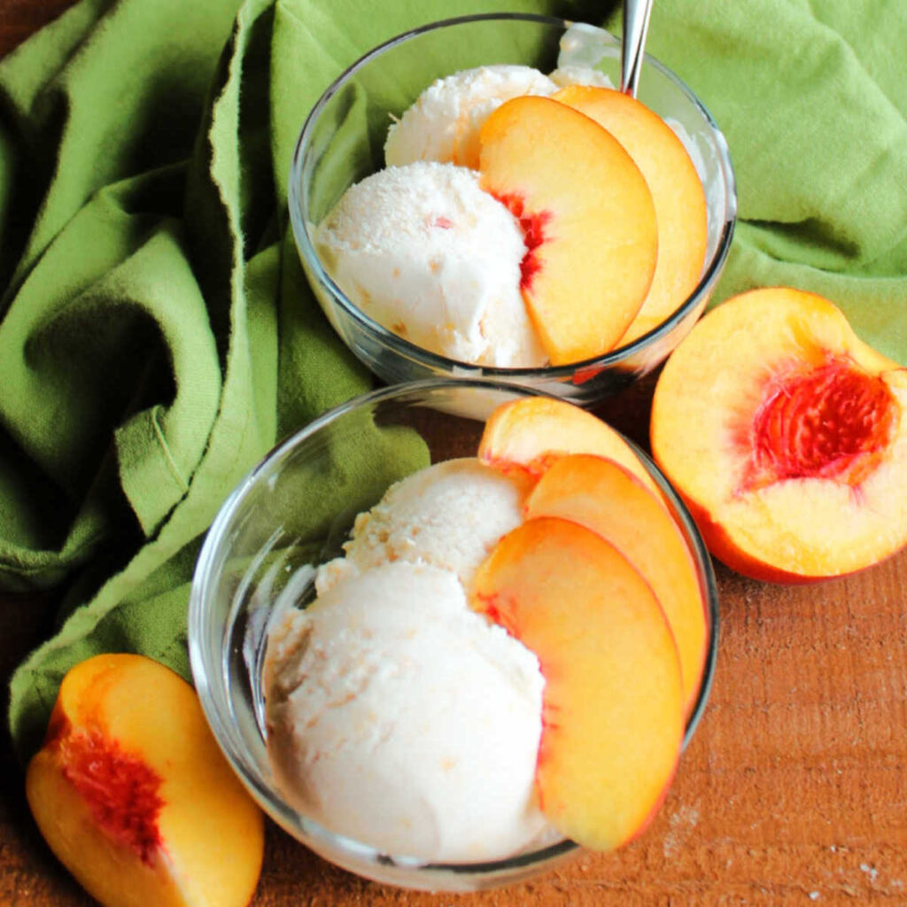 Dishes of homemade peach ice cream with slices of fresh peach on top.