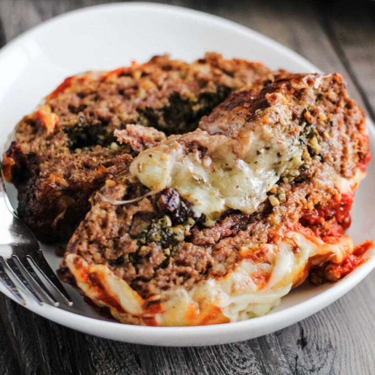 Slices of meatloaf topped with marinara and melted cheese and stuffed with more melted cheese on plate ready to eat.