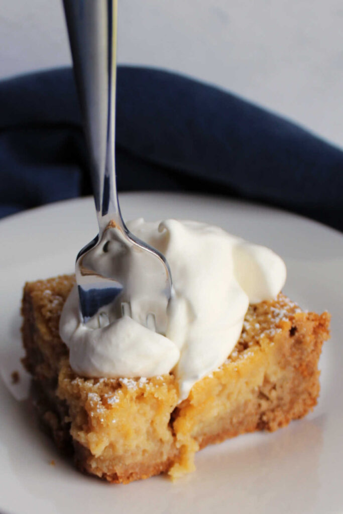 Fork going into piece of apple spice gooey butter cake topped with whipped cream.
