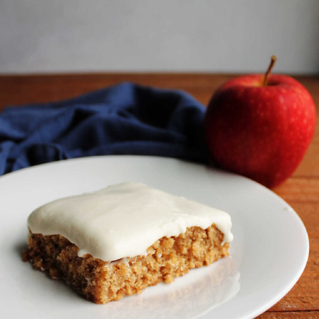 Slice of frosted applesauce bar on plate ready to eat with apple in background.