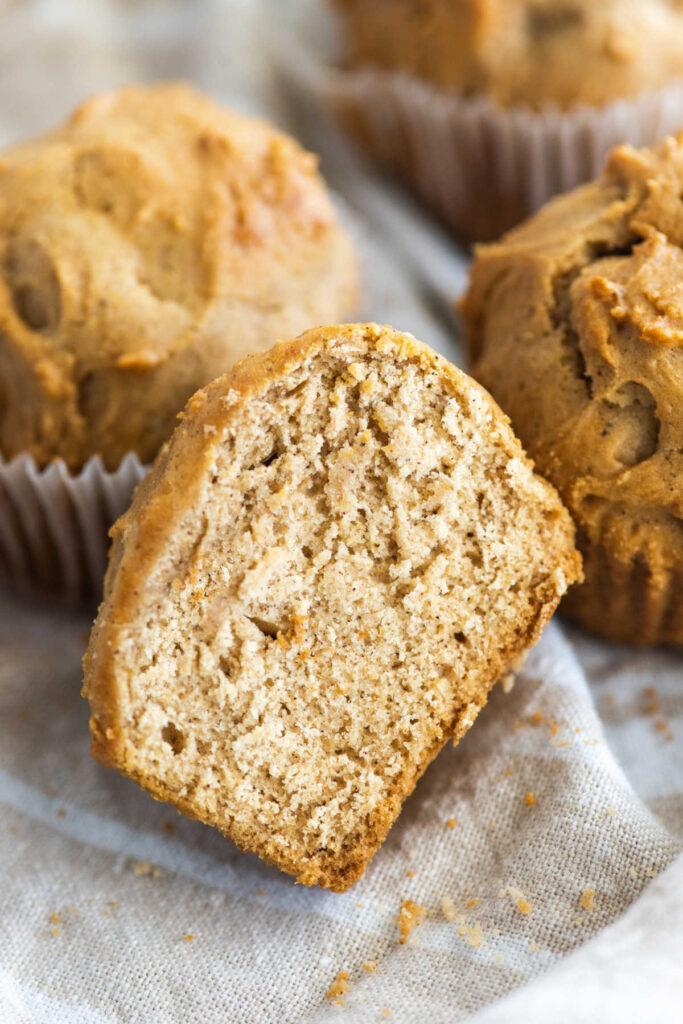 Half of orange spice muffin showing soft cinnamon speckled center.
