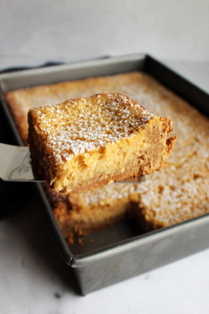 Lifting piece of apple spice gooey butter cake out of pan.