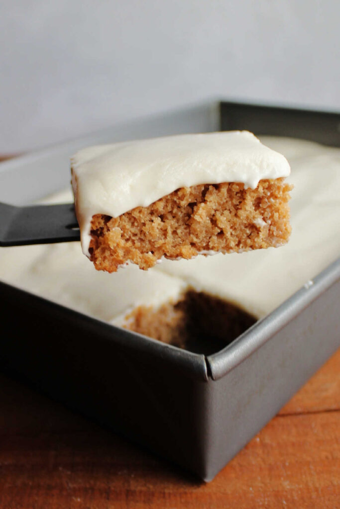 Lifting piece of applesauce bars topped with sour cream frosting out of pan.