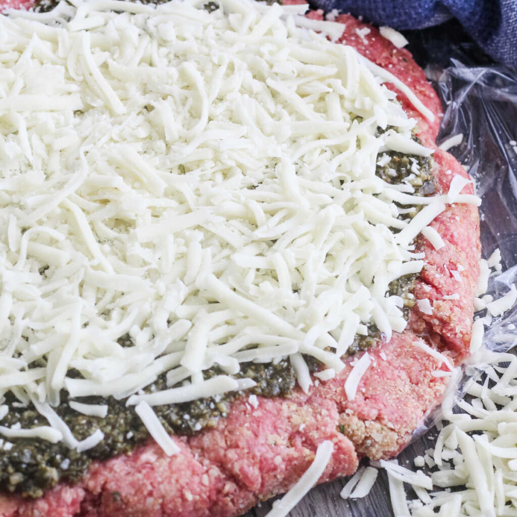Layer of ground beef covered with pesto and cheese ready to be rolled into meatloaf.