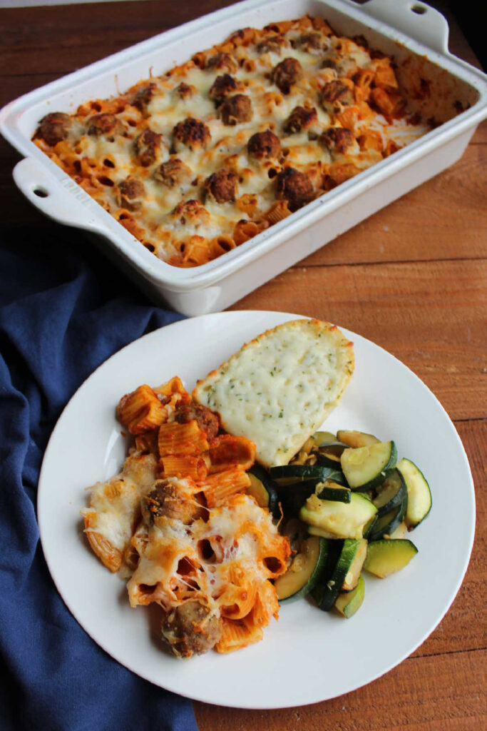 Plate of rigatoni and meatball casserole with garlic bread and zucchini next to remaining casserole.