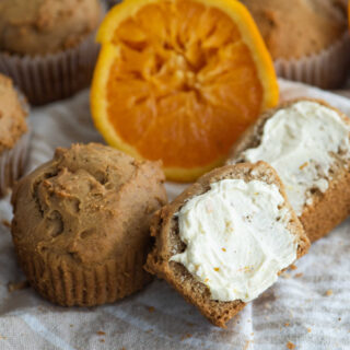 Orange spice muffin cut in half with honey butter spread over it.