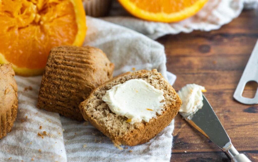 Spreading orange honey butter over muffin half.
