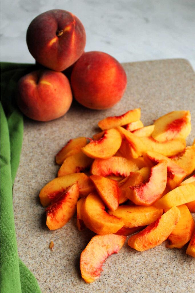 fresh peach slices on cutting board.