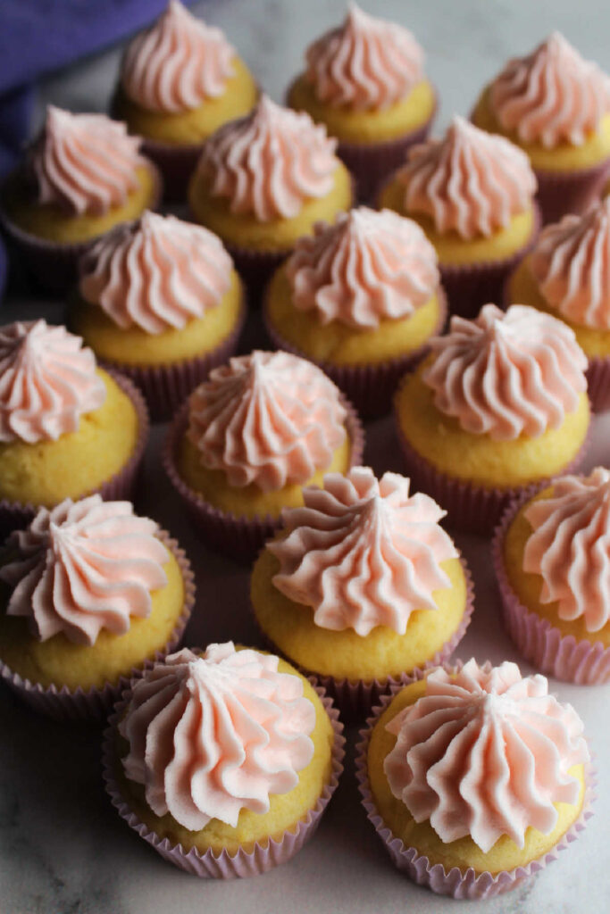 Looking down on cupcakes topped with pink lemon buttercream.
