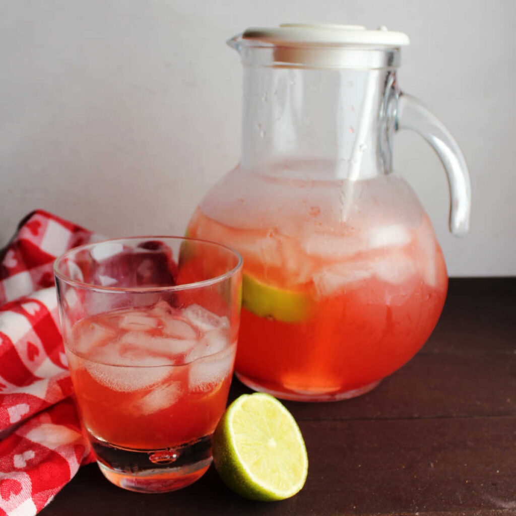 Pitcher of pink cherry limeade next to glass of limeade and a lime half.