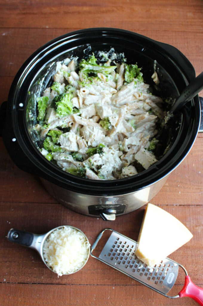 Adding grated cheese to slow cooker filled with pasta, chicken and broccoli.