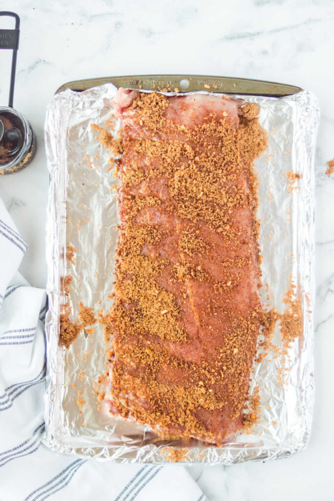 Rack of ribs coated in seasoning rub ready to cook