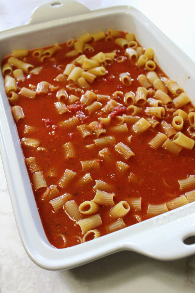 uncooked pasta and tomato sauce in baking dish ready for oven.