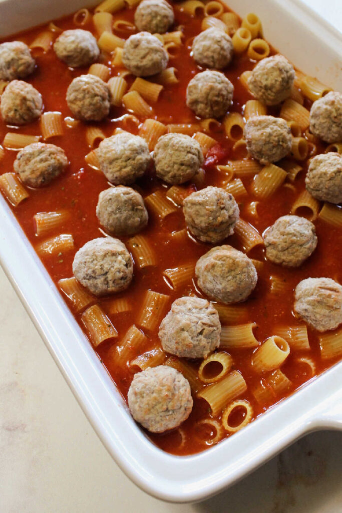 Uncooked pasta and tomato sauce in dish with frozen meatballs ready for the oven.