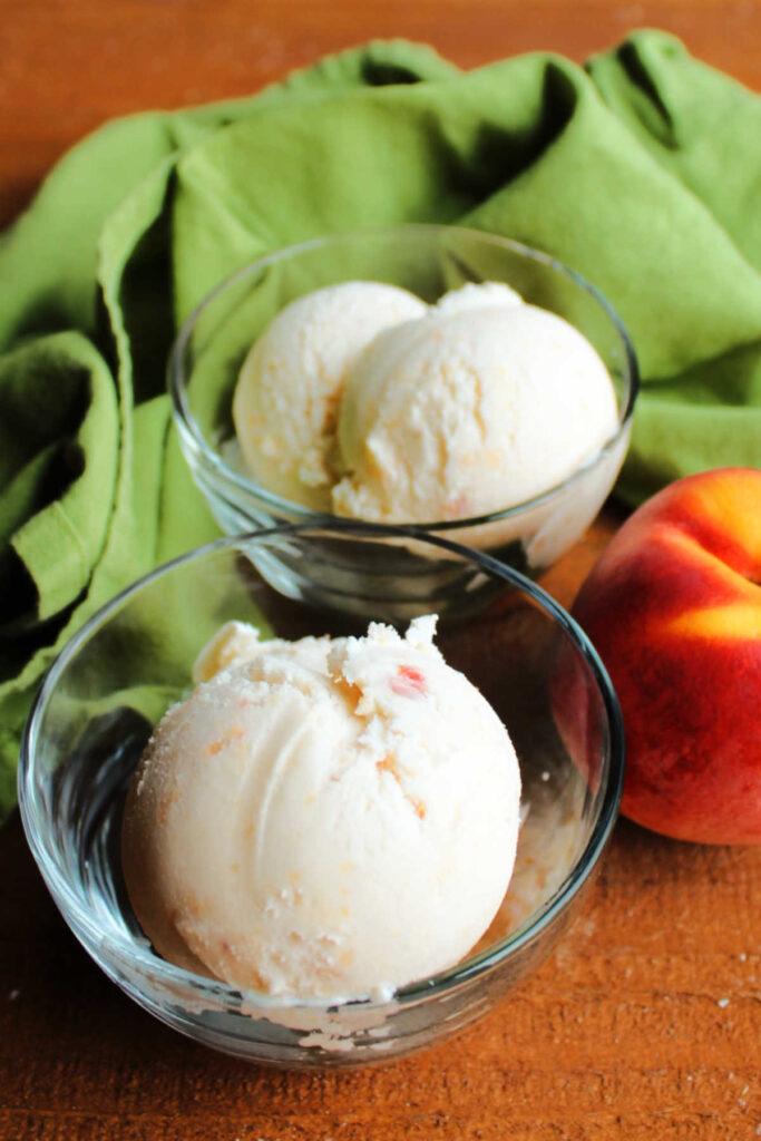 Scoops of peach ice cream next to fresh peach.