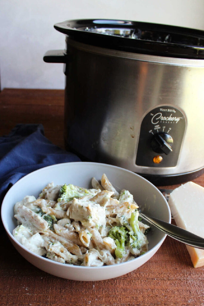 Bowl of pasta, chicken and broccoli coated in alfredo sauce in front of a crock pot.