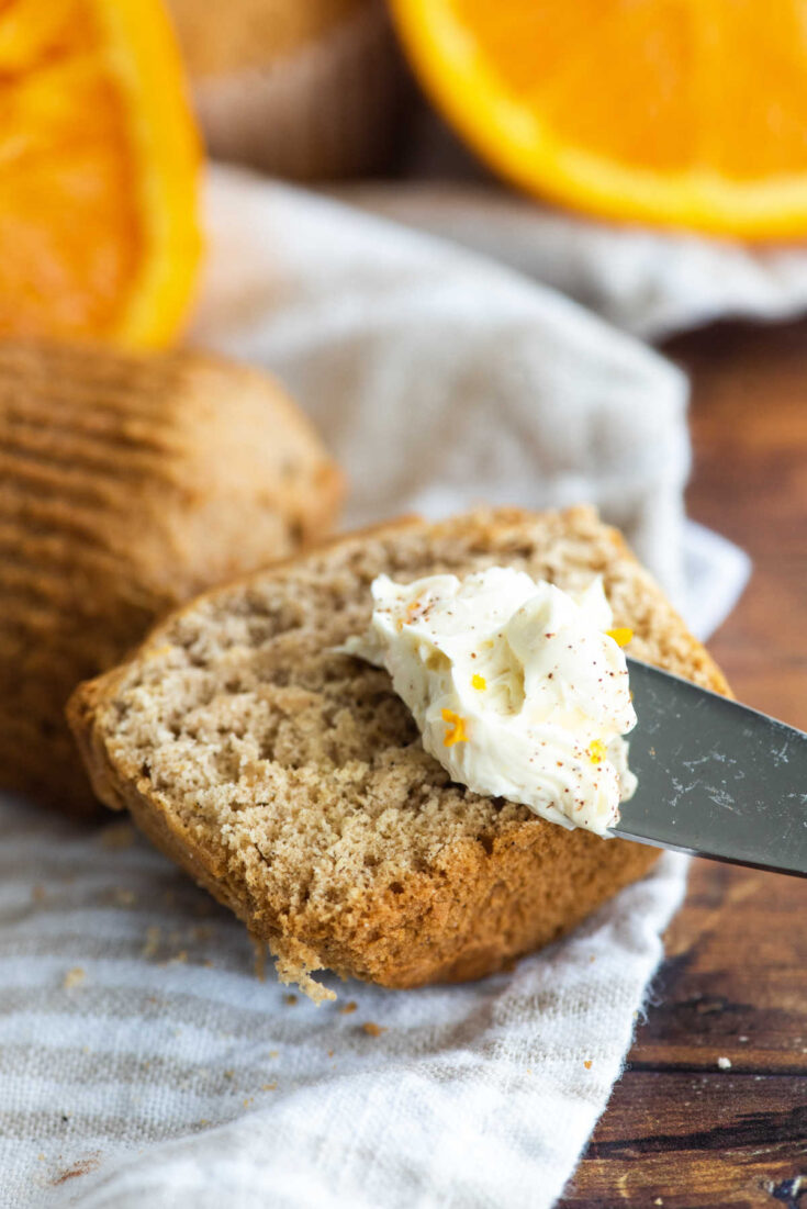 knife with orange honey butter ready to be spread over orange cinnamon muffin.