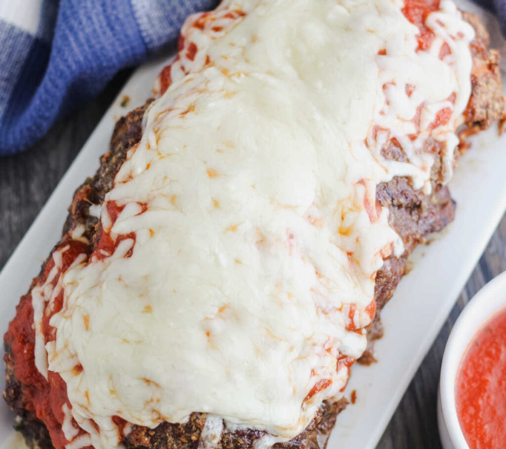 whole meatloaf topped with marinara sauce and melted cheese.