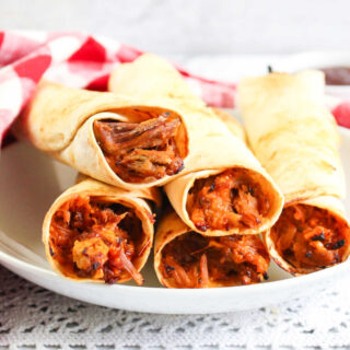 Close up of bbq pulled pork filling inside crispy tortilla taquitos, ready to eat.