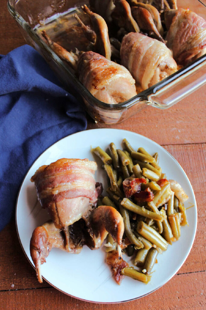 Bacon wrapped quail on plate with smothered green beans.