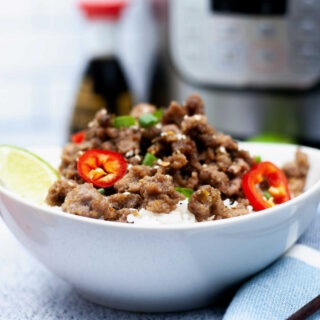 Rice bowl topped with caramel pork , sesame seeds and sliced jalapenos in front of instant pot and bottle of soy sauce.