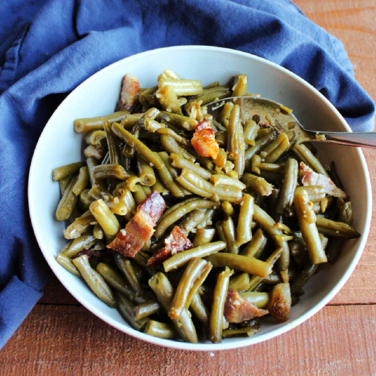 Serving bowl filled with shiny green beans and bacon smothered in sweet and sour sauce ready to eat.